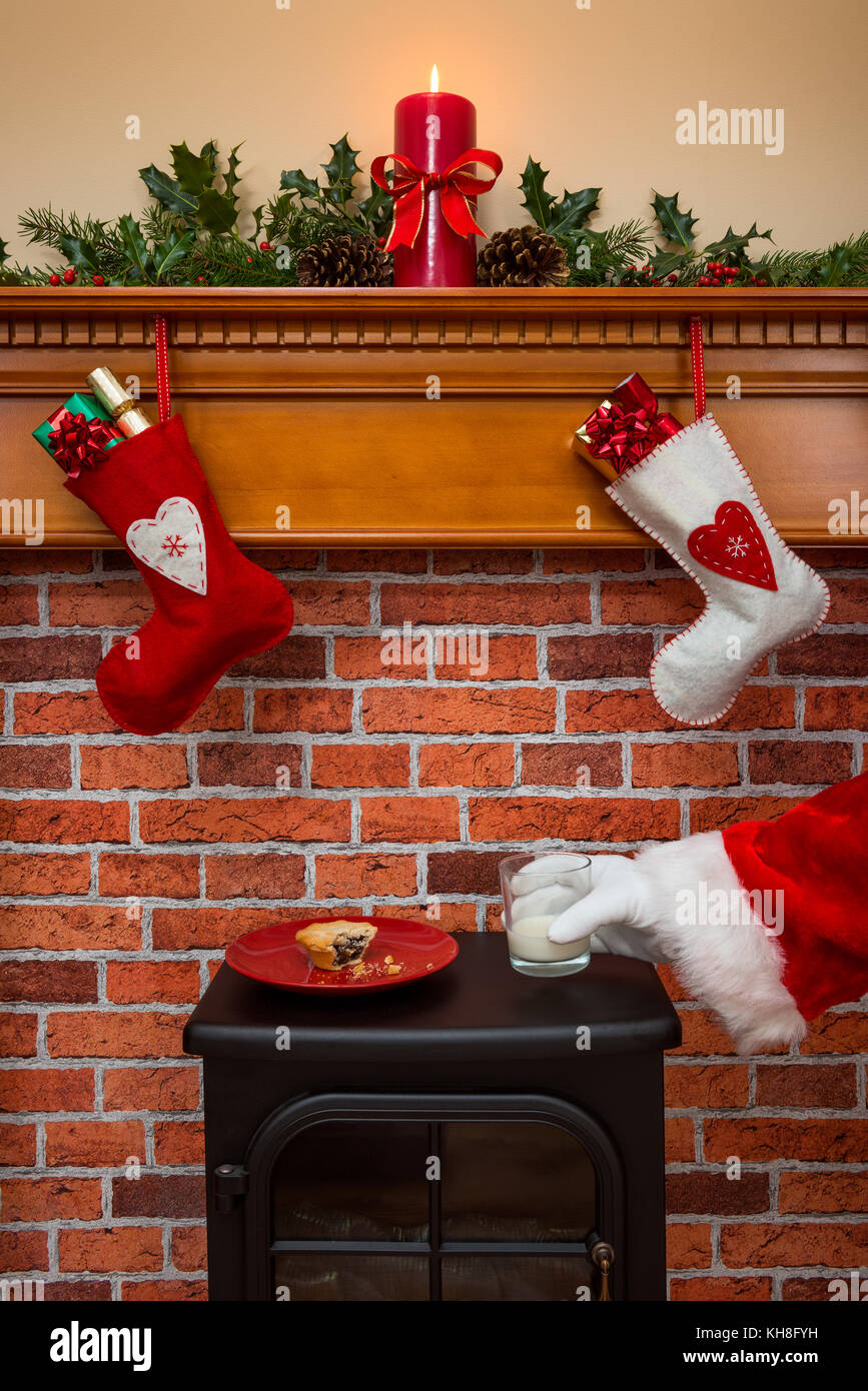 Stockings hanging over a fireplace at Christmas Eve with Santa taking a glass of milk that's been left out for - Stock Image