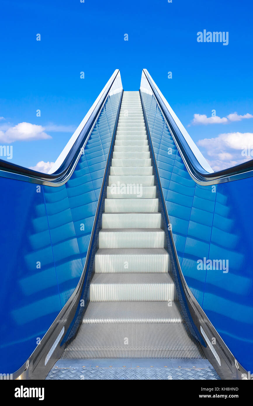 Escalator or moving stairs ascending into blue sky. Concept photo for success and climbing the job ladder. Stock Photo
