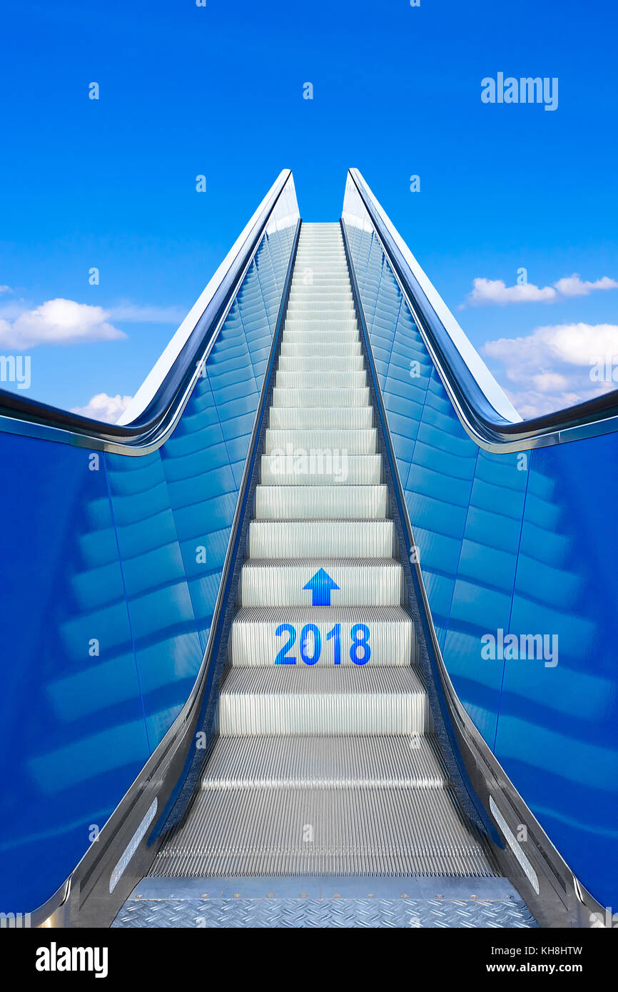 Reaching the new year 2018 on a moving stairway or escalator. Concept photo for success and reaching goals. Stock Photo