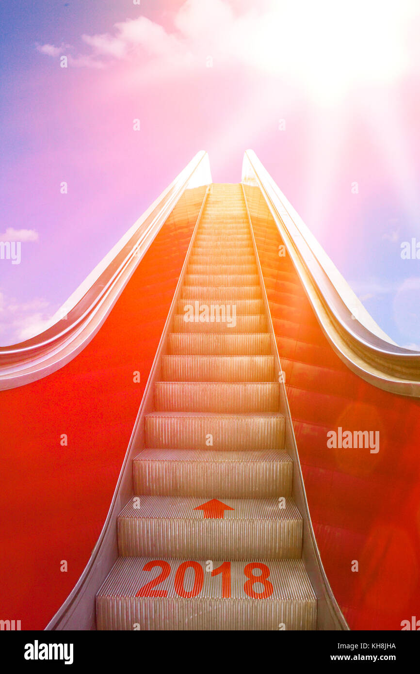 Ascending on an escalator with an arrow and 2018 written on it into sunlight. Concept photo for a successful new Stock Photo