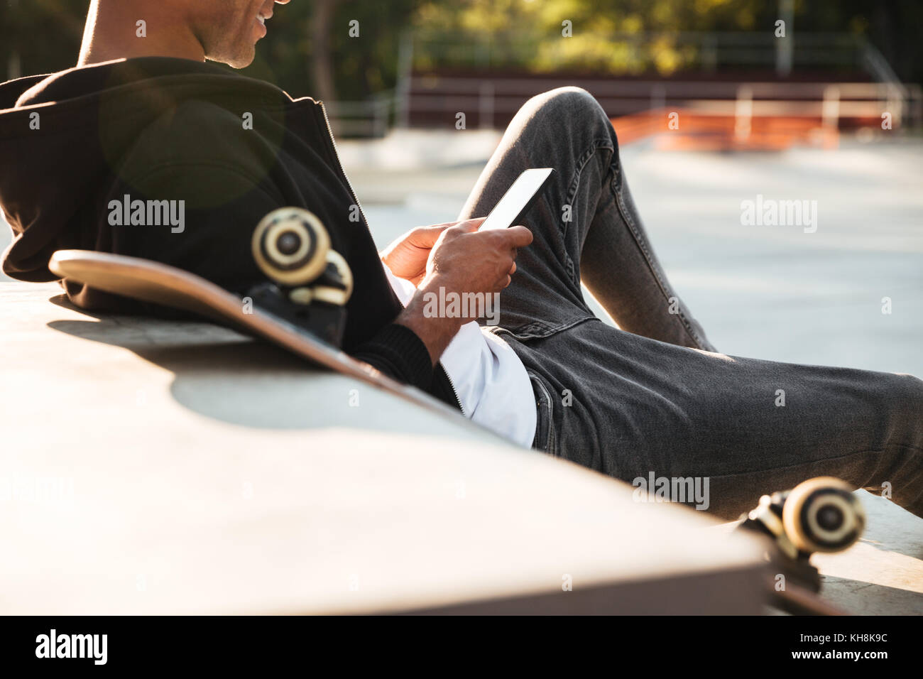 Cropped image of a smiling skateboarder looking at mobile phone screen on a sunlight background Stock Photo
