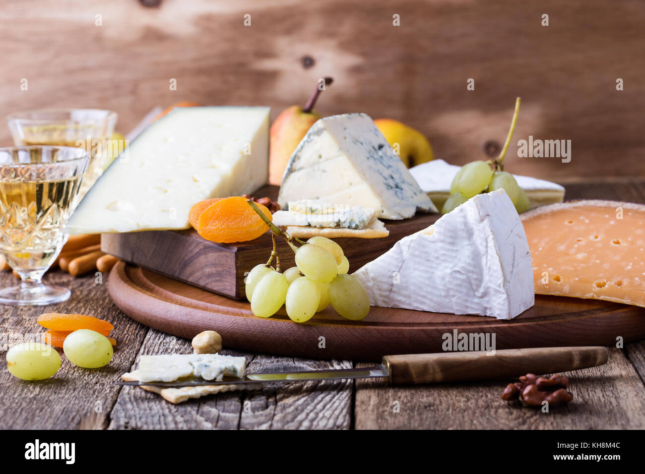 Cheese, fruit and wine wooden cutting board, delicious holiday appetizer on rustic table background - Stock Image