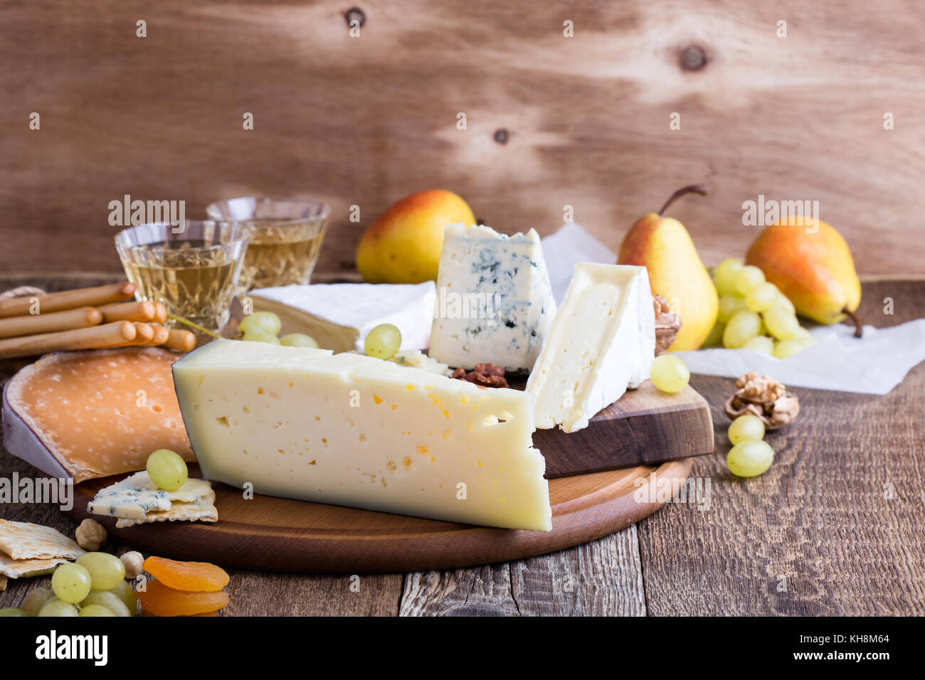 Asiago cheese. Cheese, fruit and wine wooden cutting board, delicious holiday appetizer on rustic table background - Stock Image