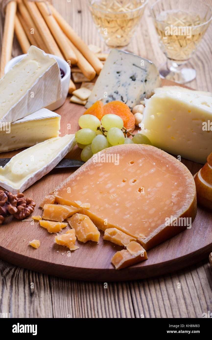 Roemer cheese. Cheese, fruit and wine wooden cutting board, delicious holiday appetizer on rustic table background - Stock Image