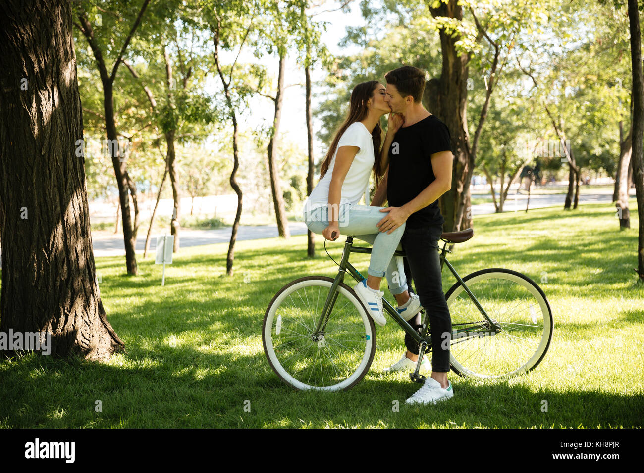Young attractive couple kissing each other while a girl in sitting on a bicycle outdoors - Stock Image