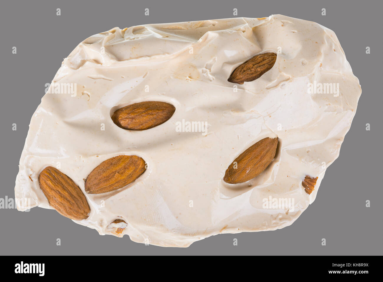 Turkish honey nougat with almonds. Piece of yummy sweet candy isolated on gray background. - Stock Image