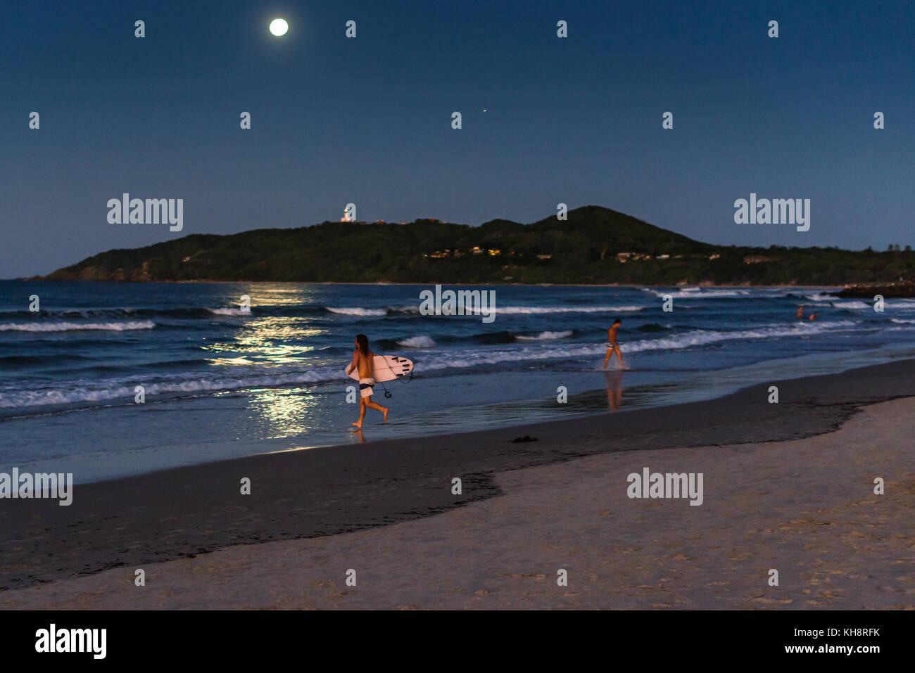 Surfing by moonlight on Belongil beach, Cape Byron Bay, New South Wales, Australia. - Stock Image