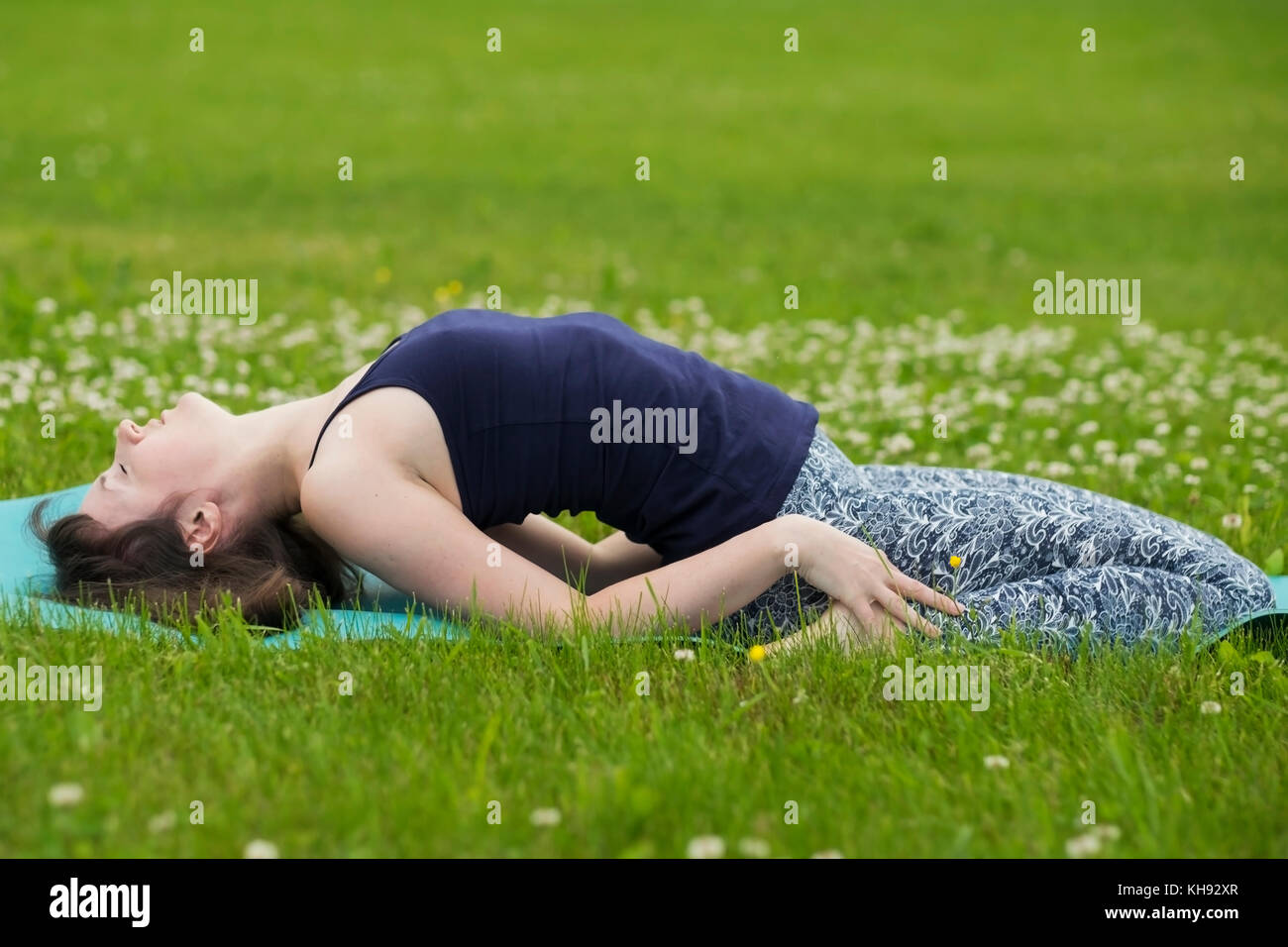 Thin girl doing yoga outside at summer on green grass. - Stock Image