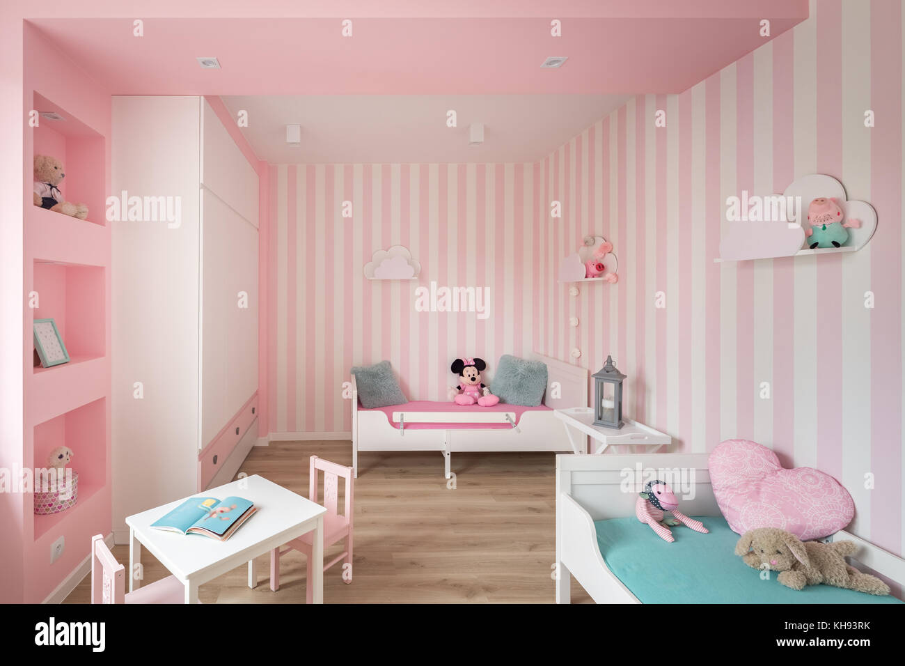 Pink Baby Room With Striped Wall And White Furniture Stock Photo