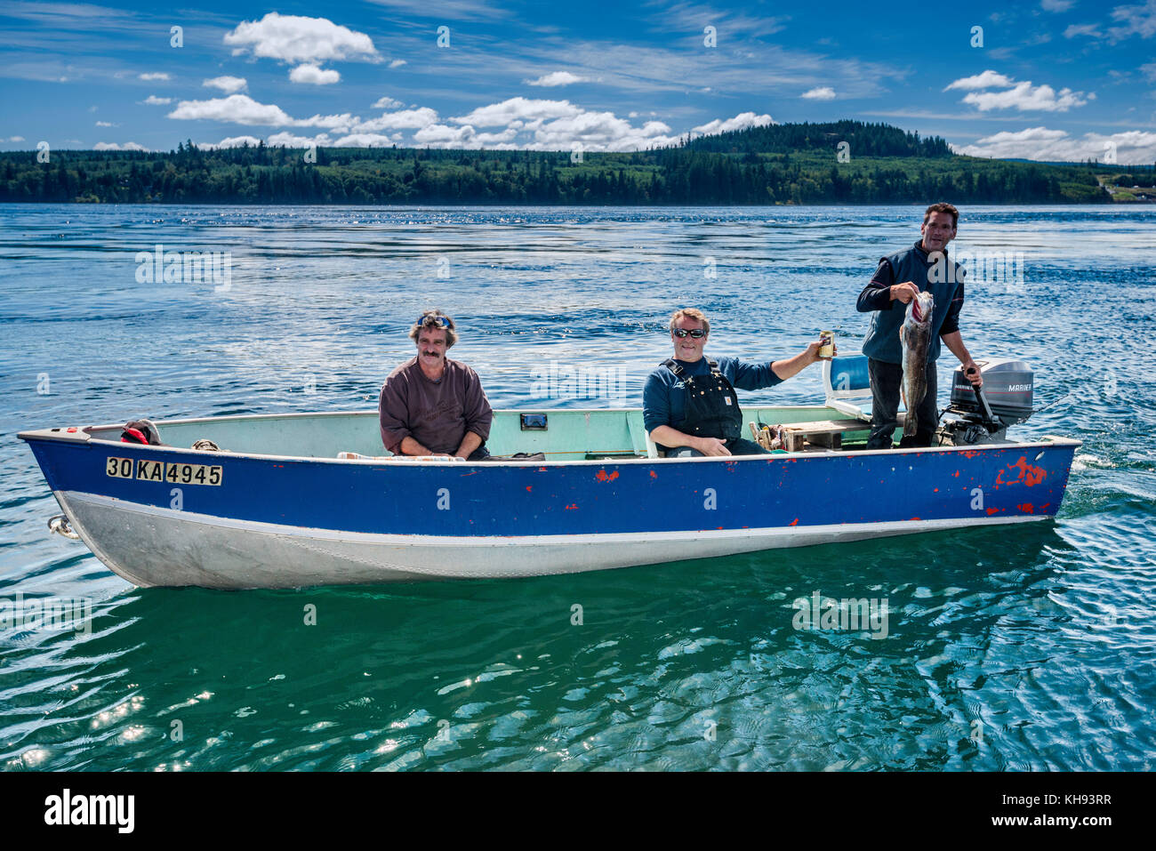 Three men showing fish they caught, salmon, in small boat, in Johnstone Strait off Vancouver Island, British Columbia, - Stock Image