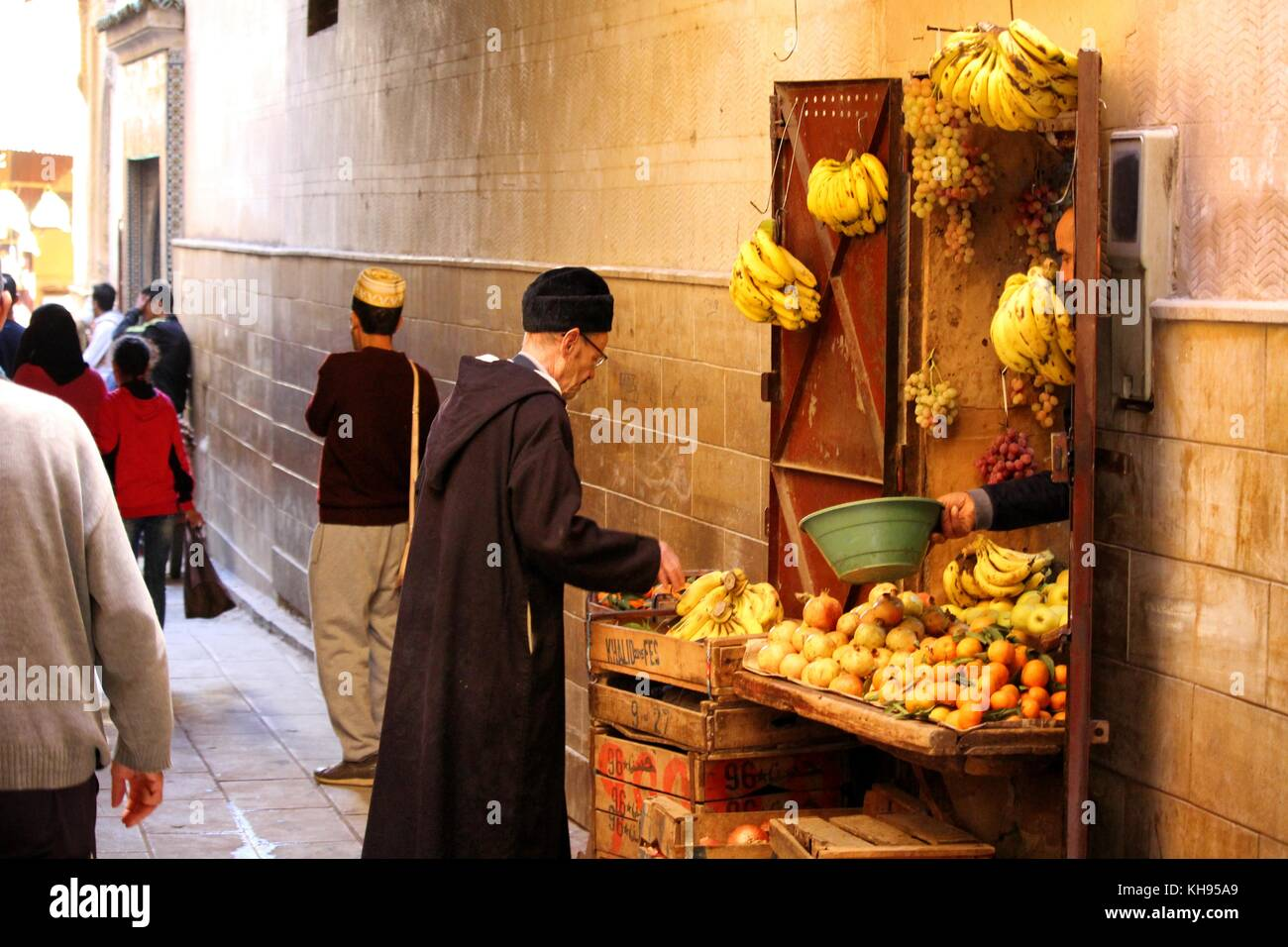 Fez, Morrocco - November 8, 2017: Local people buying goods at a street fruit and vegetables market in the Fez Medina - Stock Image