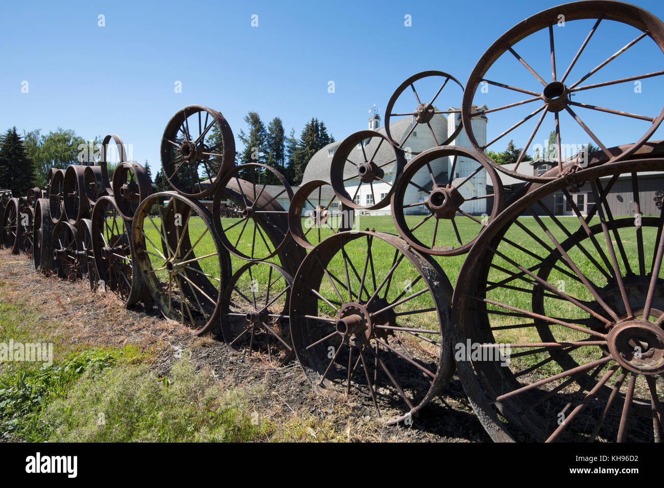 Old farm fence made of old rusty wagon & tractor wheels at the Artisans at the Dahmen Barn is on the Palouse - Stock Image