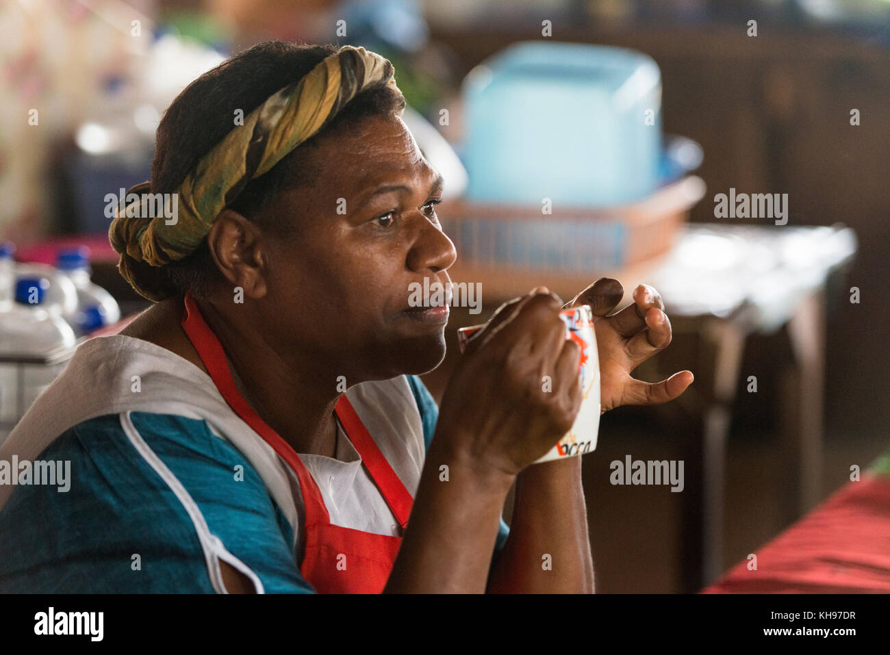 Joanna drinking a cup of hot water. Joanna works at Port Vila Fruit and Vegetable Market, Vanuatu. Stock Photo