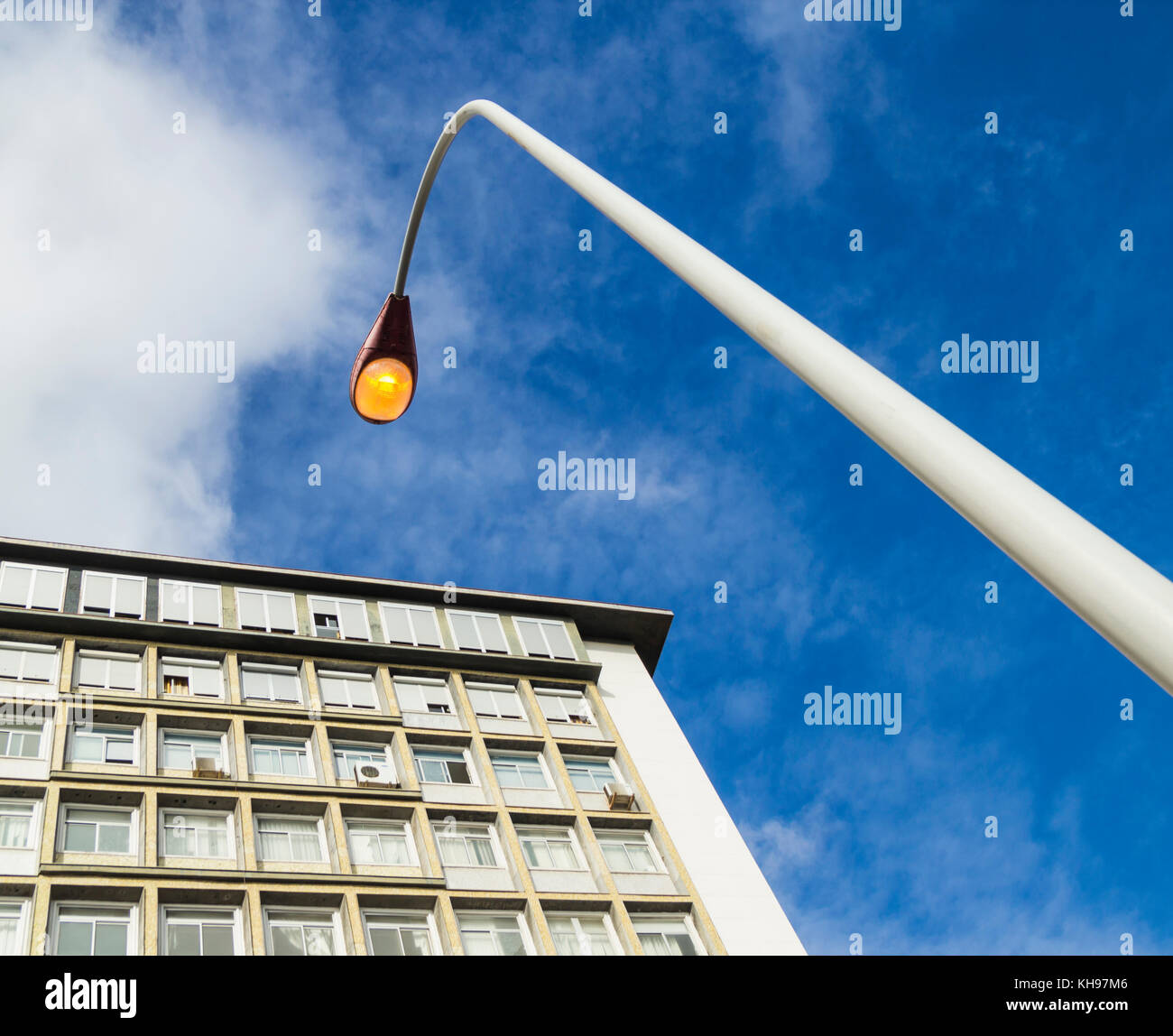 Street lighting on during day. - Stock Image