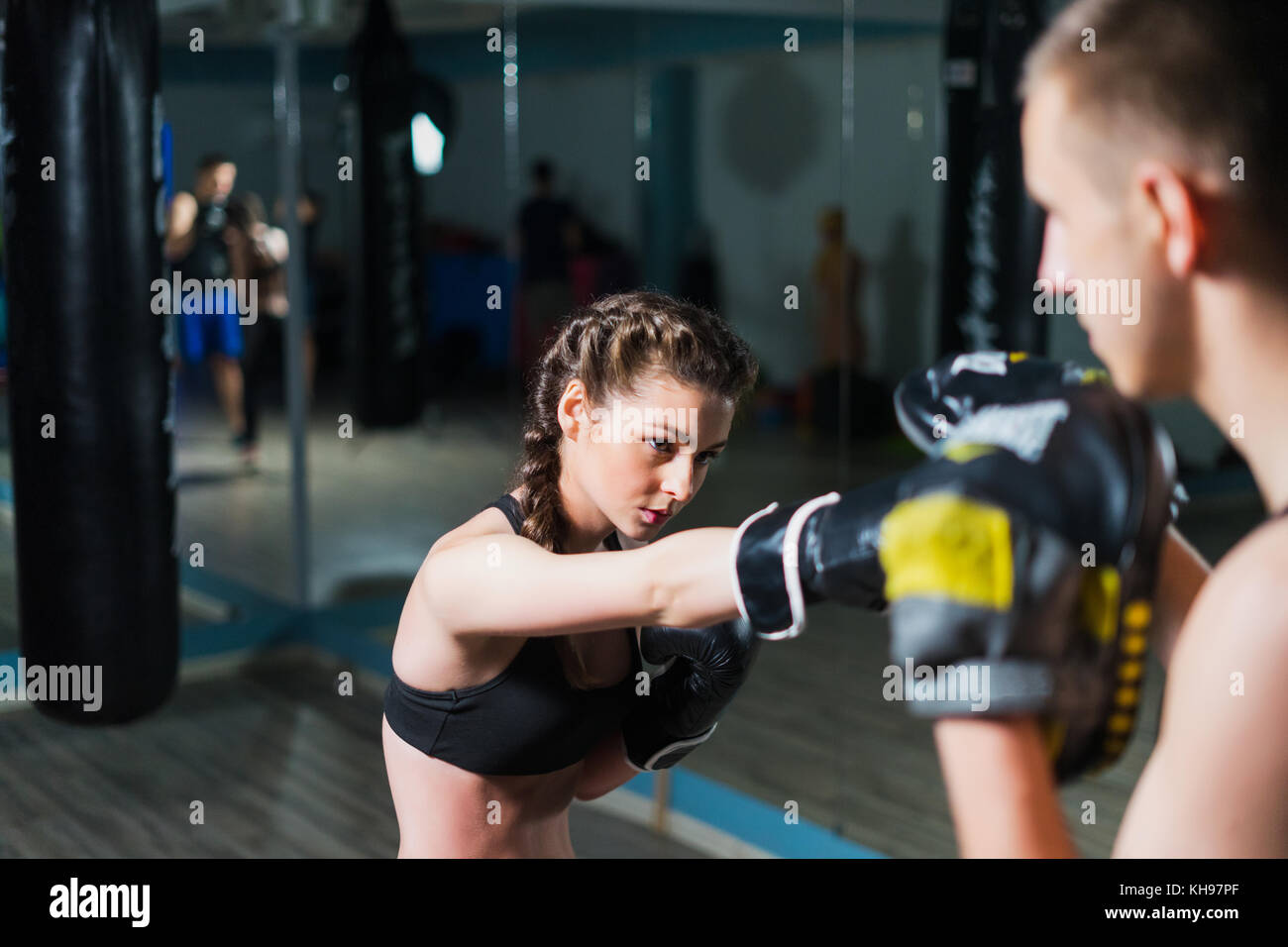 Young fighter boxer fit girl wearing boxing gloves in training   - Stock Image