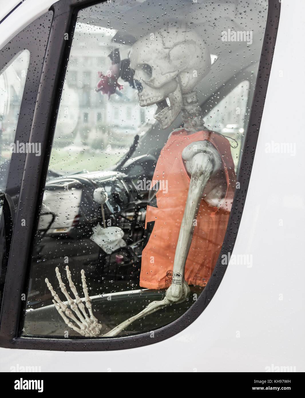 Skeleton in passenger seat of parked van. - Stock Image