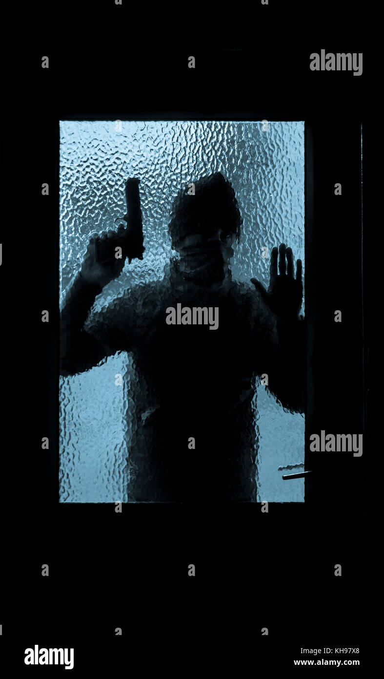 Man holding gun looking through glass pane of house door. Concept image for gun violence, armed robbery, gun crime, - Stock Image