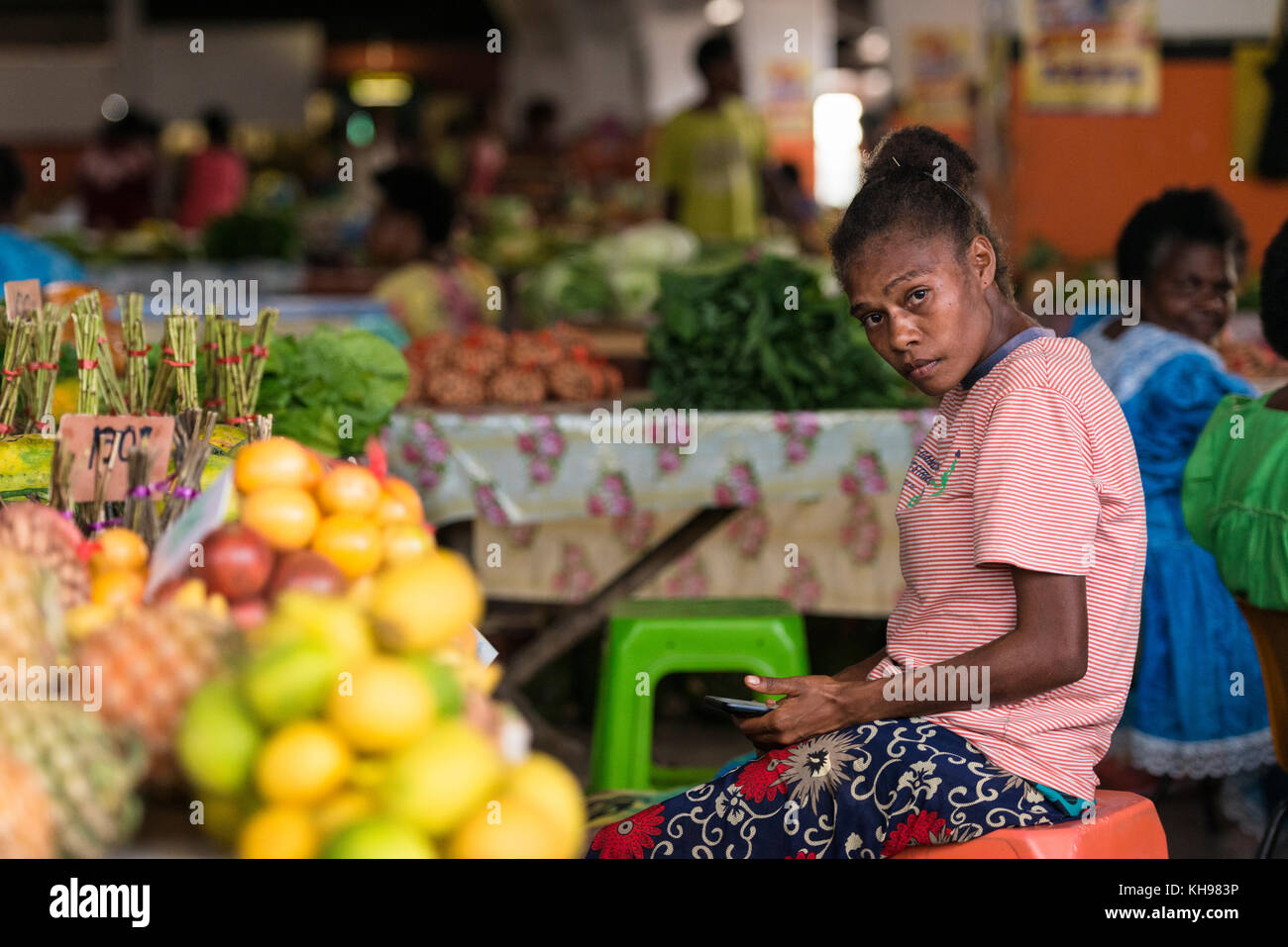 Young woman stallholder sitting with her mobile phone, Port Vila Fruit and Vegetable Market. Vanuatu. Stock Photo