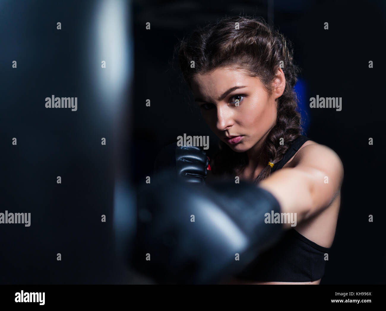 Beautiful  fighter boxer girl in training with heavy punching ba - Stock Image