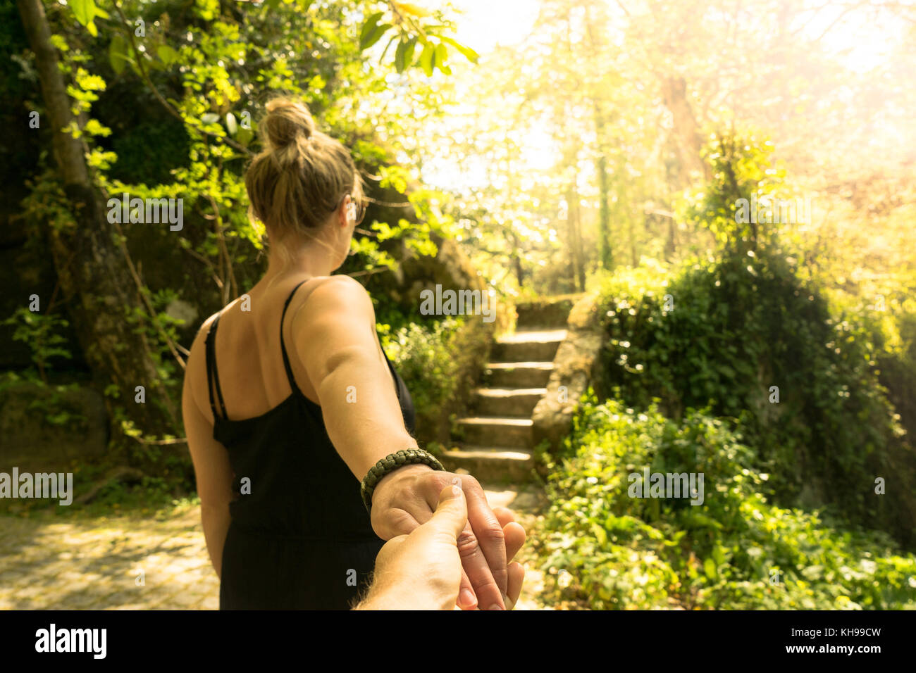 Coulple holding hands in a garden. Walking together toward stairs. - Stock Image