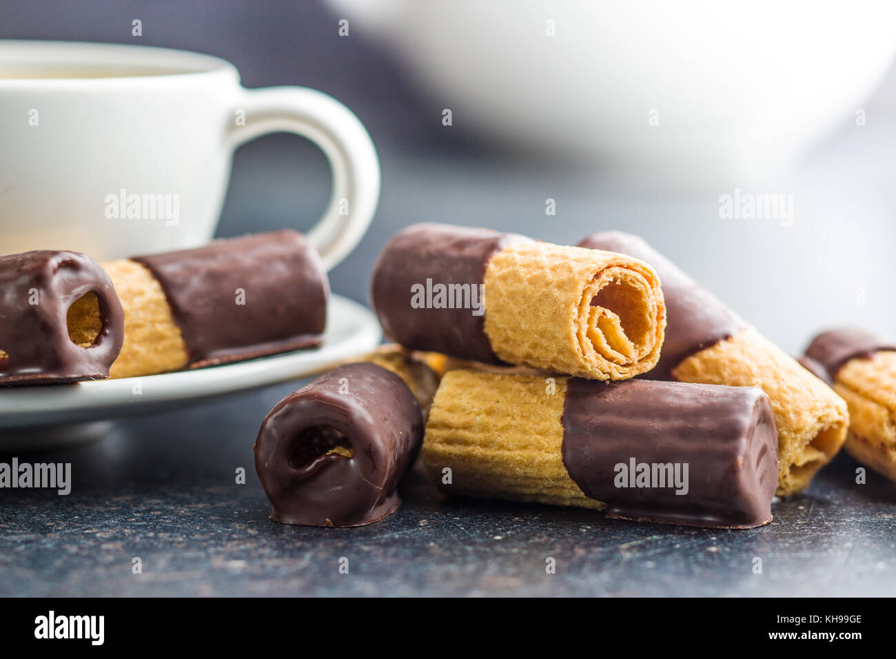 Sweet dessert. Biscuits rolls with chocolate icing on old kitchen table. - Stock Image