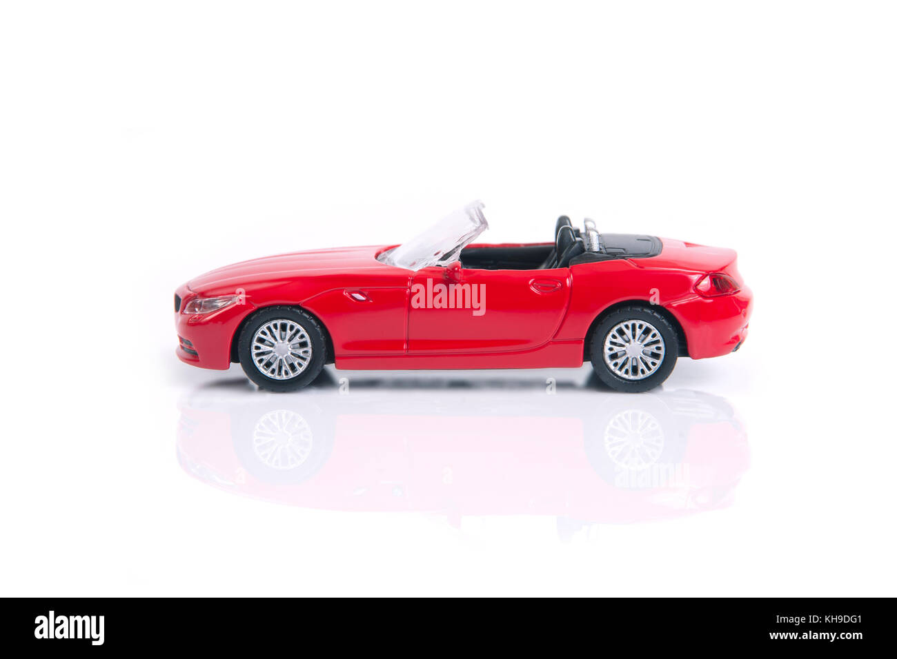 Red toy or model convertible sport car on white background. - Stock Image