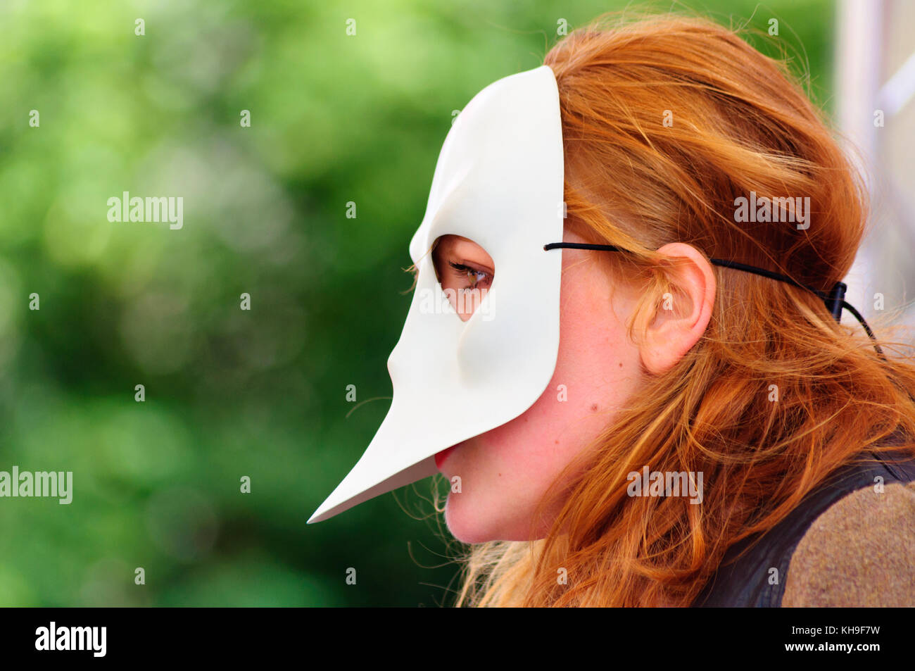 Closeup of a female performer with red hair wearing a mask on the Royal Mile during the Edinburgh International Fringe Festival Stock Photo