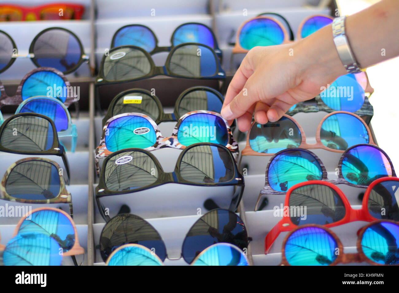 Choosing a cheap sunglass at a street market vendror. - Stock Image