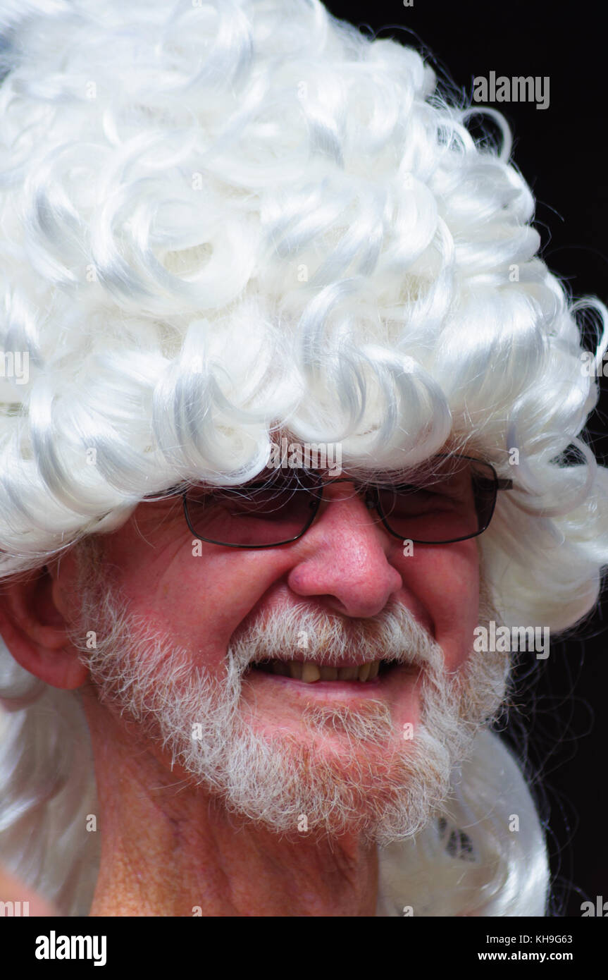 Male performer with a beard and wearing sunglasses and  a white wig on the Royal Mile during the Edinburgh International Stock Photo
