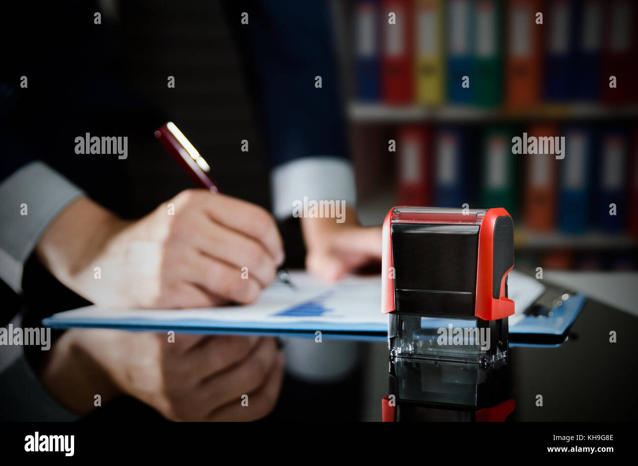 Businessman working with documents. Automatic stamp in foreground. accountant analysis working budget sign accounting - Stock Photo