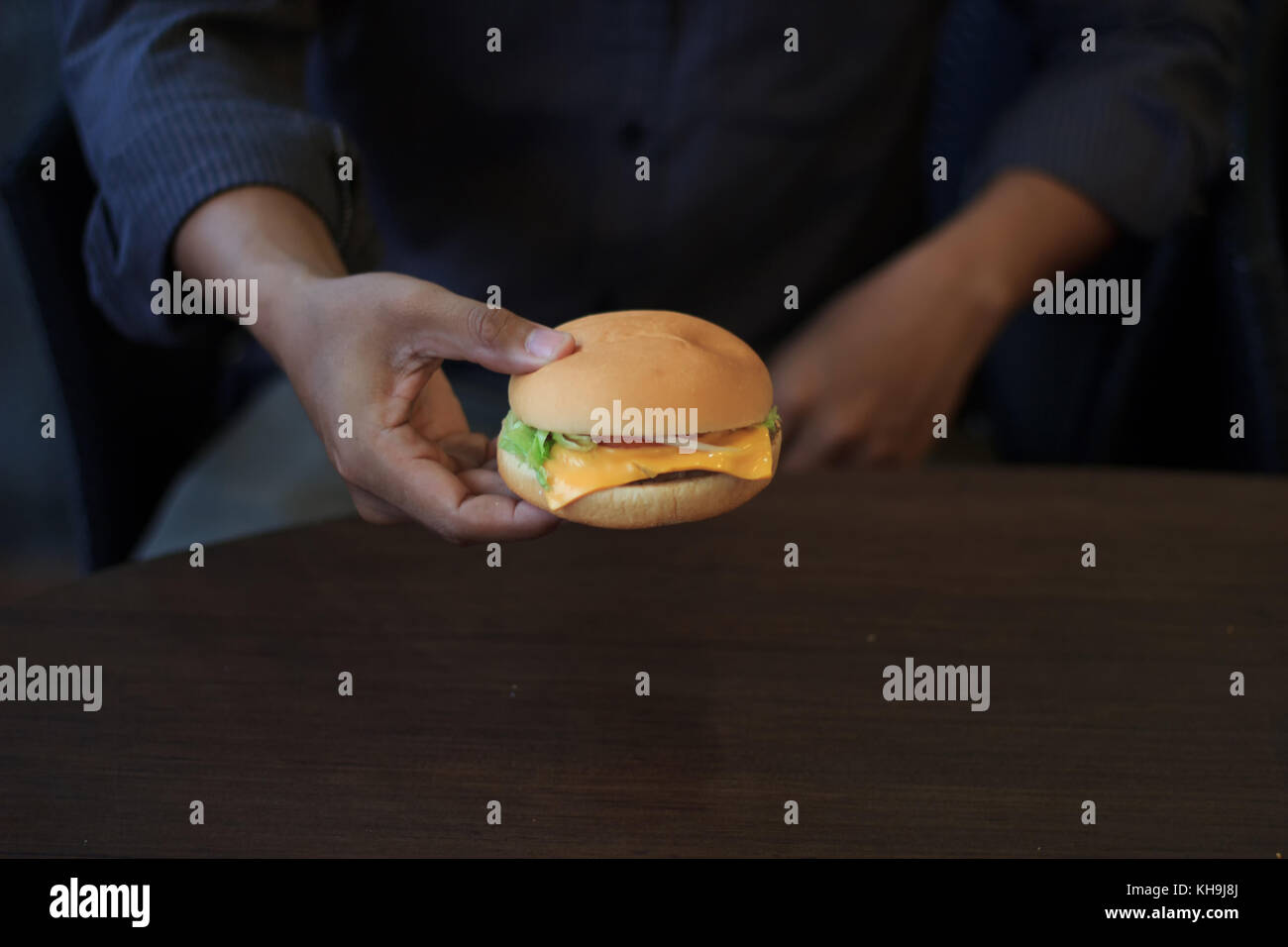 Young man hands fast food burger select focus and blur background low light or underexposed, Young man holds burger - Stock Image