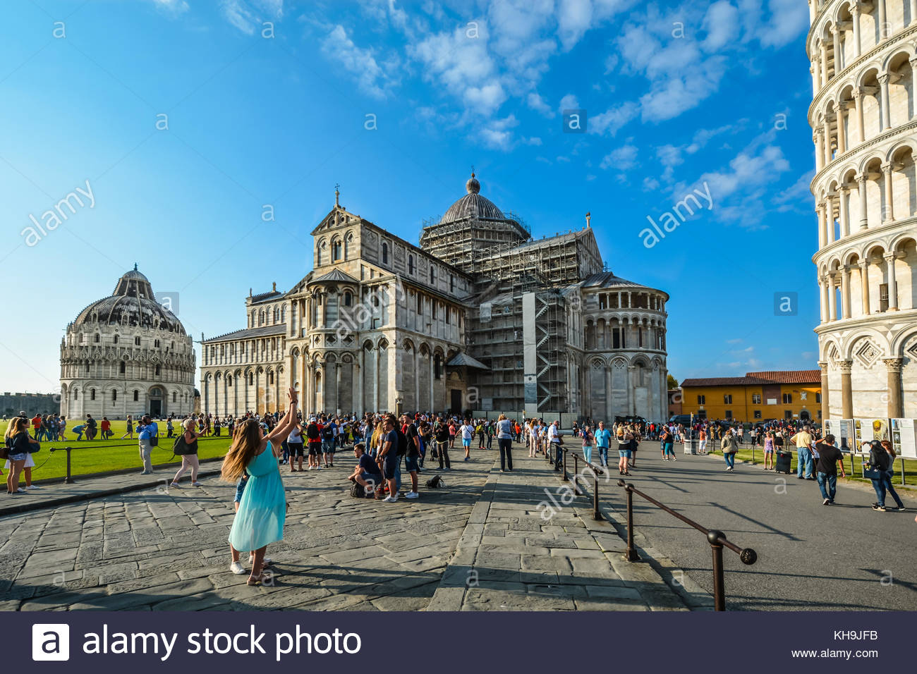 A girl gestures in a dancelike way as she poses in front of the Leaning Tower of Pisa on the PIazza Dei Miracoli Stock Photo