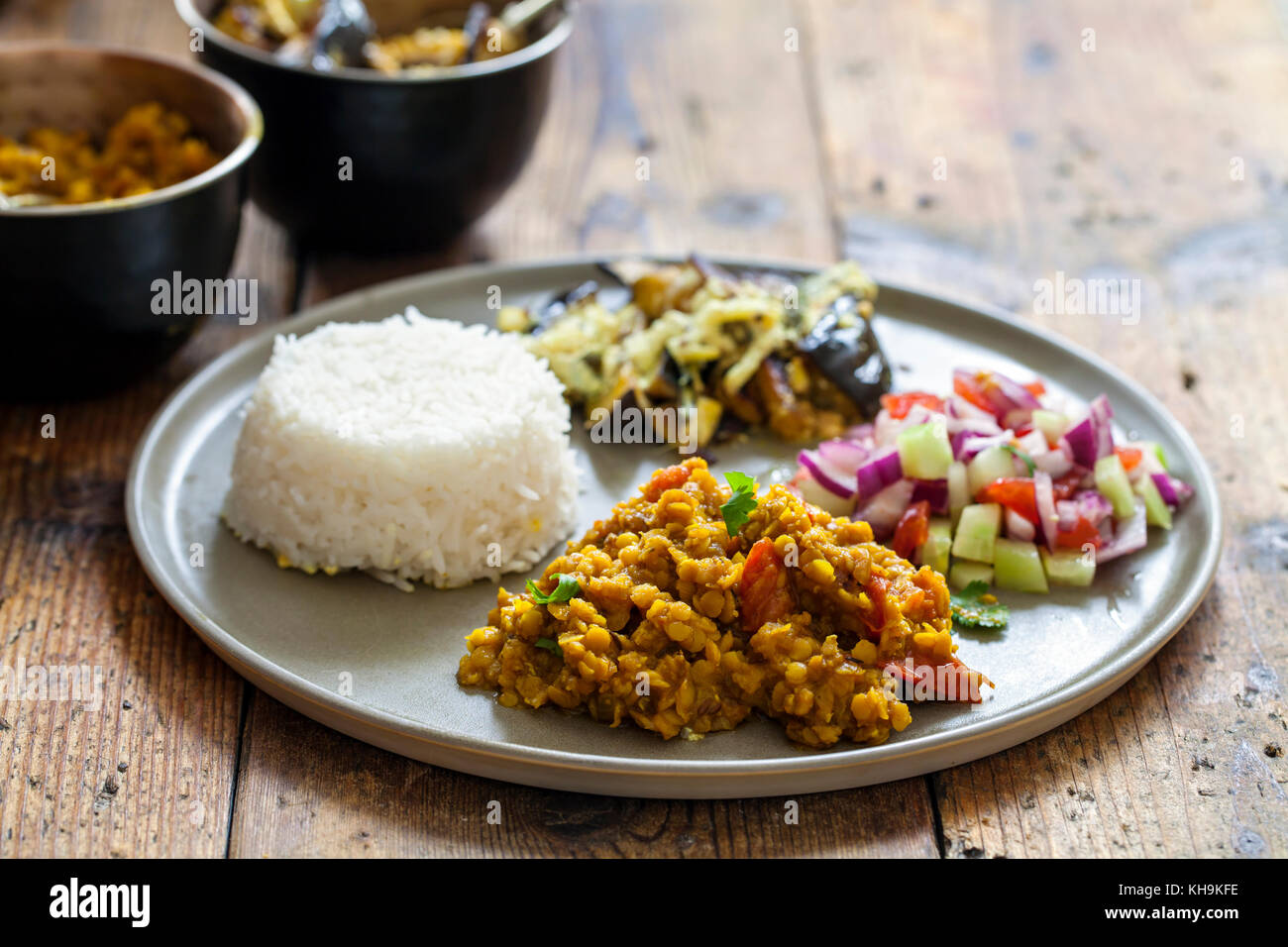 Indian meal with masoor dal - lentil curry, dahi baingan, rice and salad - Stock Image