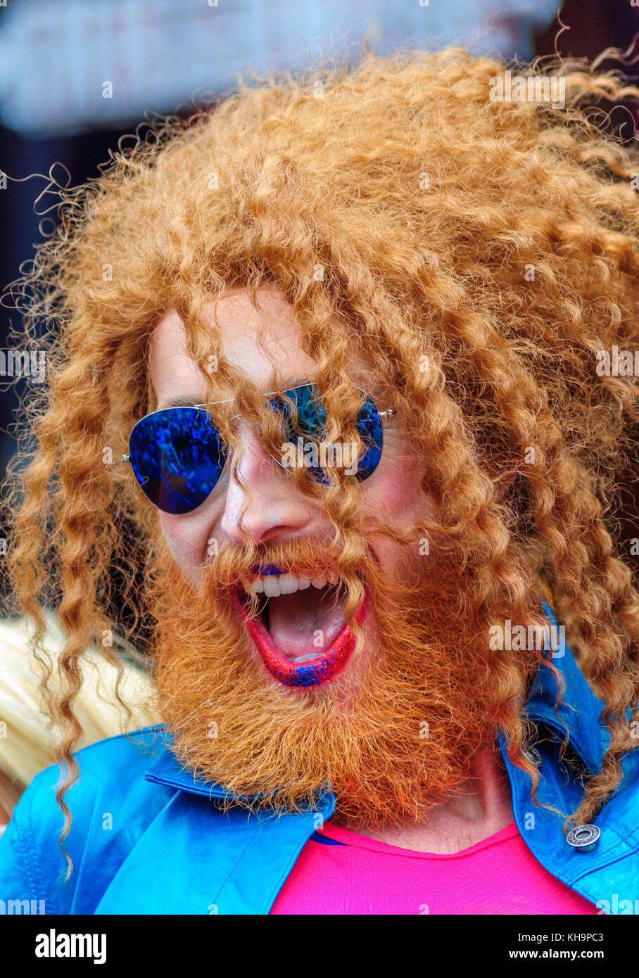 7ft tall drag artist Gingzilla with ginger braided hair, beard and moustache wearing blue mirror sunglasses during - Stock Image