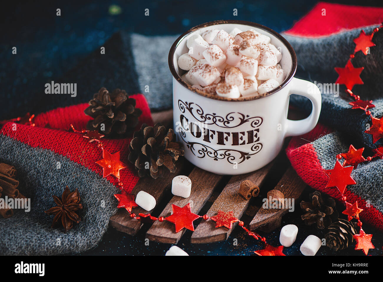 Christmas hot cocoa with marshmallows, cinnamon, knitted scarf, stars, pine cones and garlands on a warm wooden - Stock Image