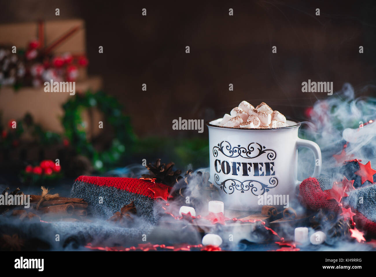 Hot chocolate with marshmallows in a cozy enamel mug with steam and Christmas decorations - Stock Image
