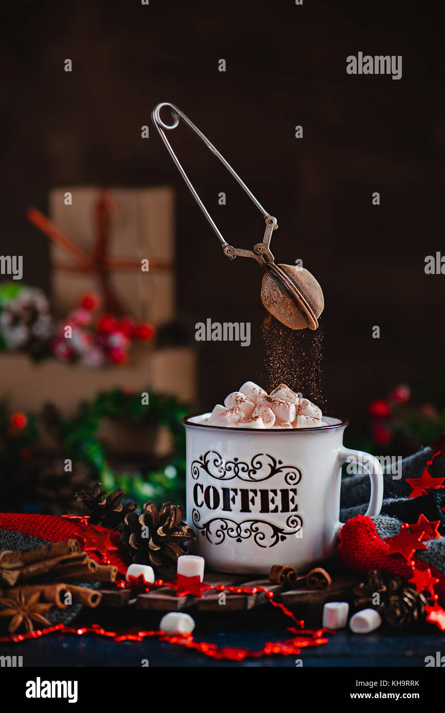 Hot chocolate with marshmallows and flying cocoa powder in Christmas scene with gifts. Action photography with flying Stock Photo
