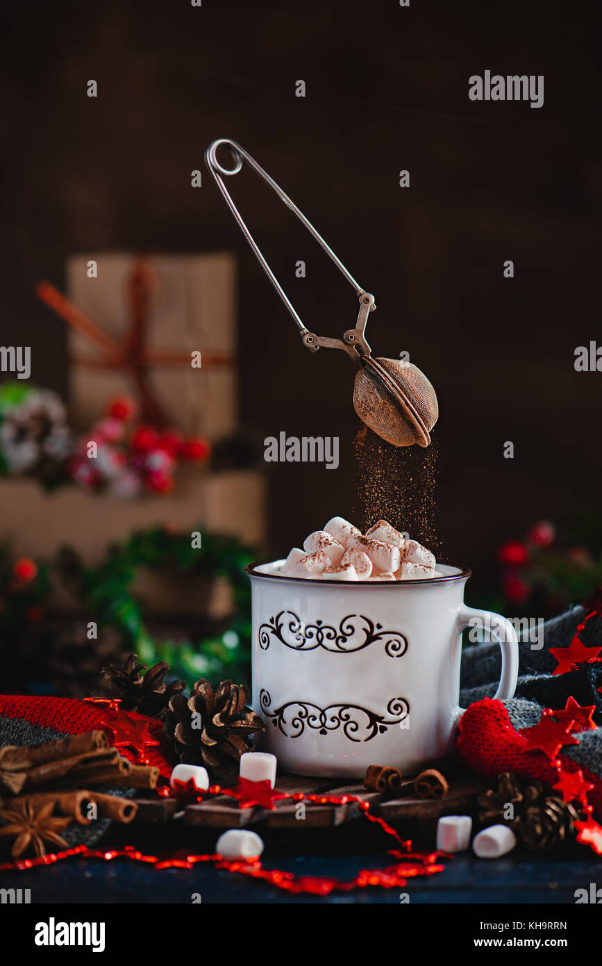 Hot chocolate with marshmallows and flying cocoa powder in Christmas scene with gifts. Action photography with flying - Stock Image