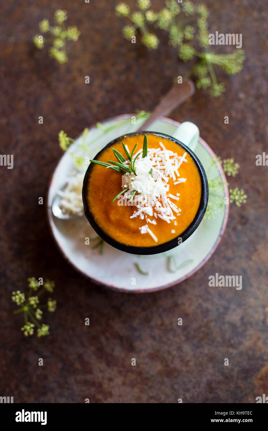 Close up of delicious pureed tomato soup garnished with grated cheese and fresh rosemary - Stock Image