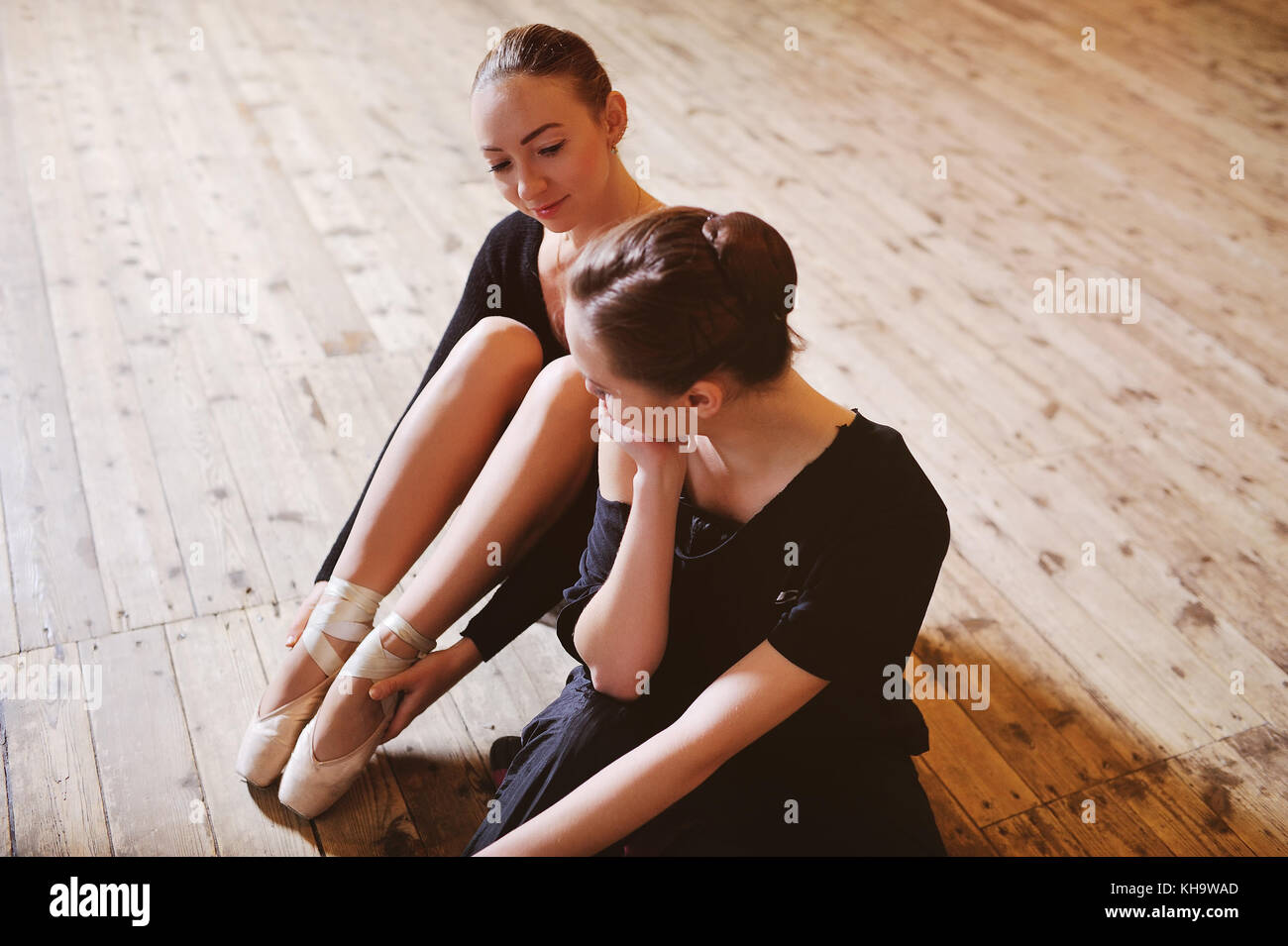 two ballerinas talking and smiling sitting on a wooden floor - Stock Image