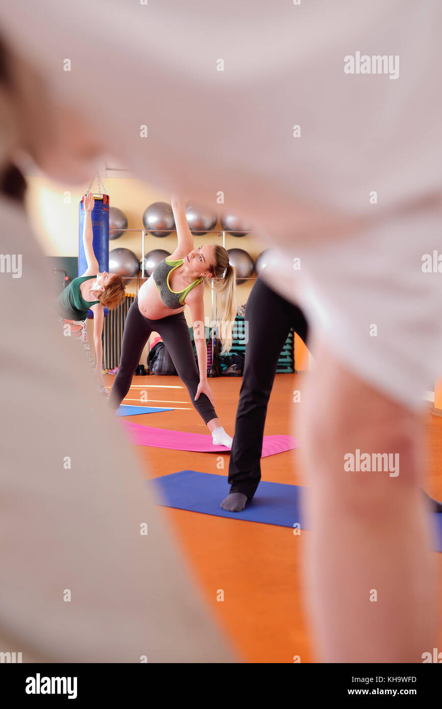 pregnant girl engaged in fitness together with a group of yoga in a sports club - Stock Image