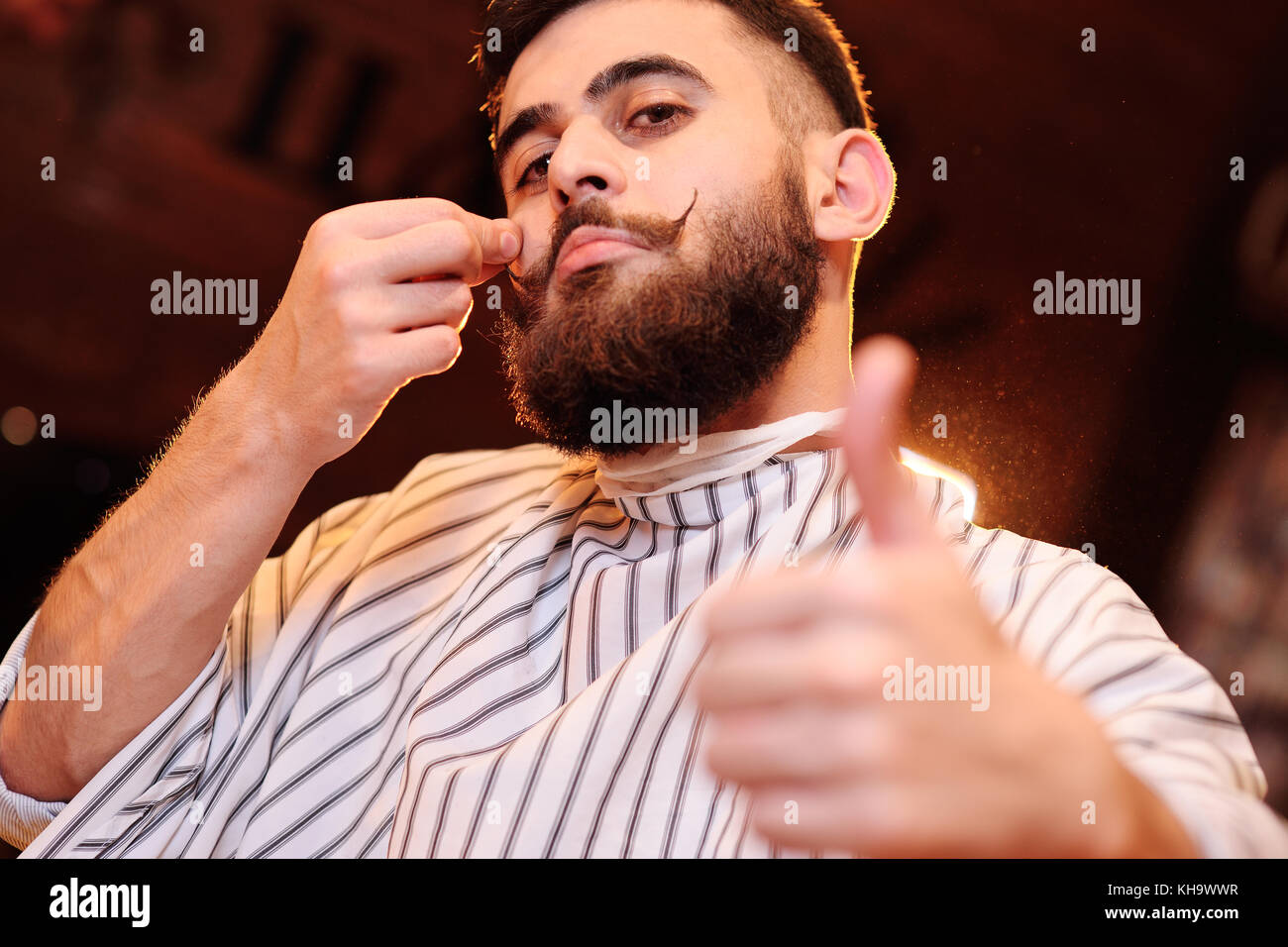 man with beautiful mustache and beard sitting in an armchair in barbershop Stock Photo