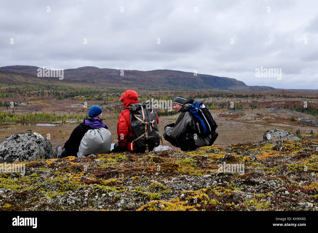 Three hikers sitting down, enjoying the arctic tundra view Mistastin Lake Larbrador, Canada. - Stock Image