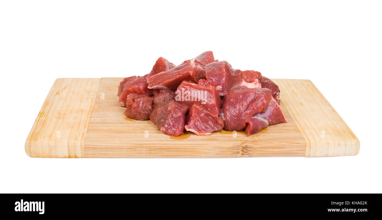fresh meat on a wooden cutting board isolated on white background - Stock Image