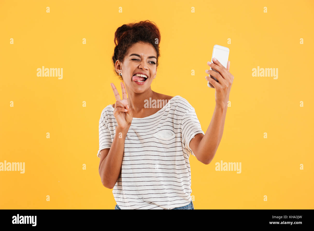 Young funny african casual lady grimacing and making selfie on smartphone isolated over yellow - Stock Image