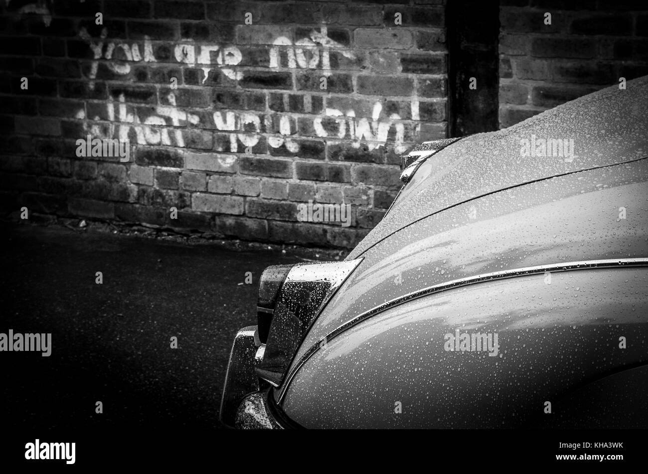 Mk2 Jaguar parked in an run down  industrial zone with graffti quoting you are not what you own. - Stock Image