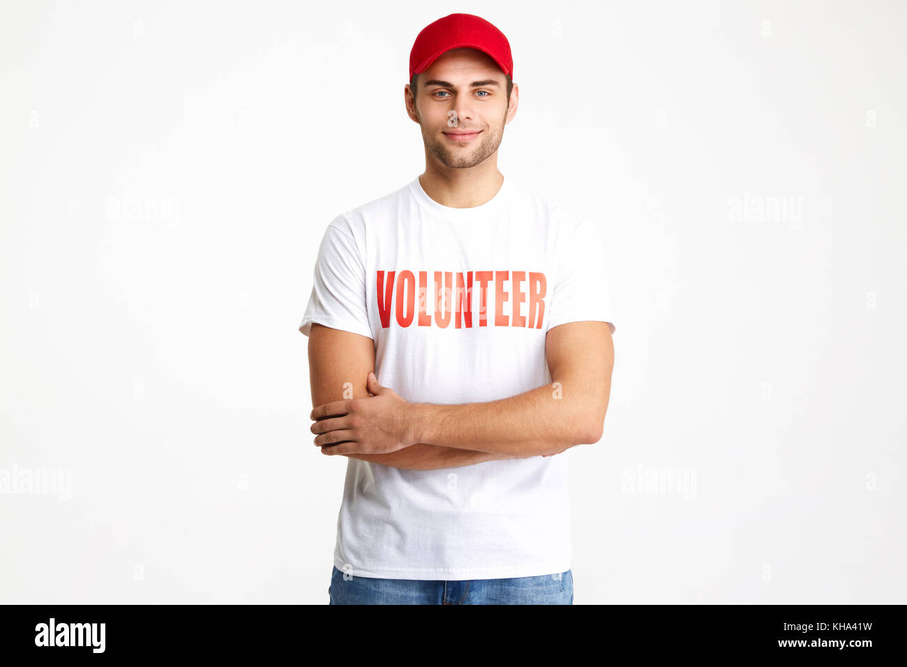Portrait of a confident smiling man wearing volunteer t-shirt standing with arms folded and looking at camera isolated - Stock Image