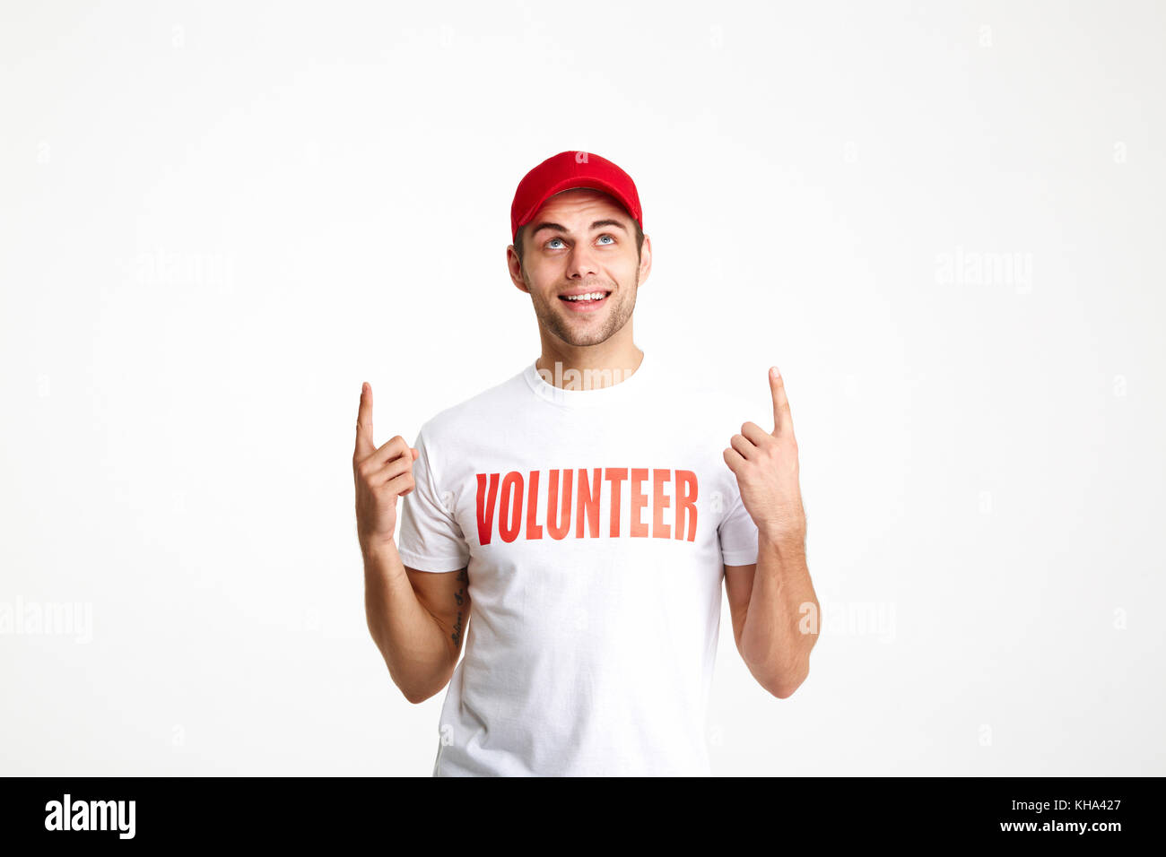 Portrait of a young man wearing volunteer t-shirt pointing two fingers up at copy space isolated over white background - Stock Image