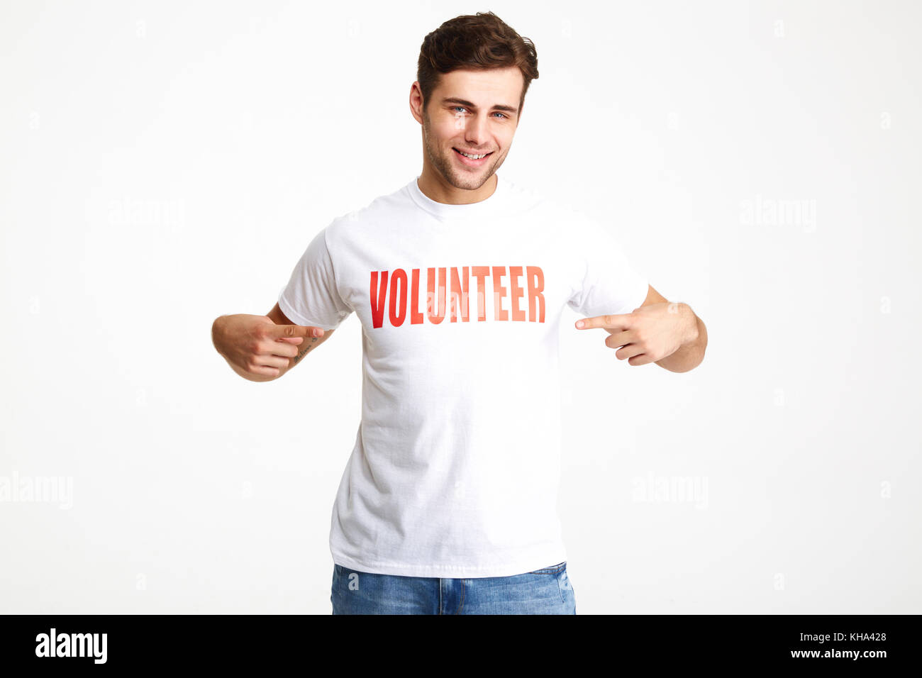 Portrait of a smiling confident man wearing volunteer t-shirt pointing two fingers isolated over white background - Stock Image