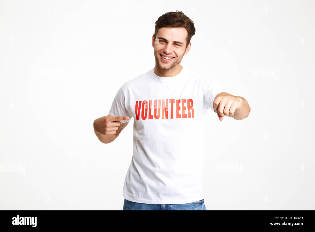 Portrait of a happy cheerful man wearing volunteer t-shirt pointing two fingers isolated over white background - Stock Image